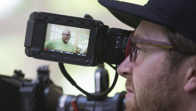 An NFL Films videographer shoots Bruce Arians talking at the Arians' home in Greensboro, GA on June 28, 2015.
