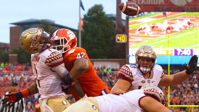 Clemson, SC, USA; Florida State Seminoles quarterback James Blackman (1) fumbles the ball after being defended by Clemson Tigers defensive end Clelin Ferrell (99) and defensive lineman Christian Wilkins (42) during the second quarter of the game at Clemson Memorial Stadium.