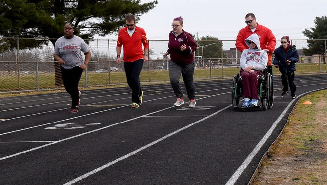 Athletes and coaches warm up together during a practice of Newark's unified track team, which pairs students with Special Olympics participants.