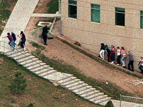 Police officers point weapons at a building as students take cover and flee the area outside Columbine High School in Littleton Colo., during a shooting rampage by two students on April 20, 1999.