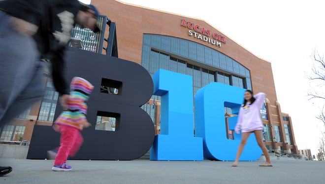 Big Ten football fans walk by the Big Ten logo out front of Lucas Oil Stadium Friday afternoon in preparation for this the Big Ten football championship game Saturday evening. The Big Ten Fan Fest will also be open Saturday from 10 a.m. to 8 p.m.