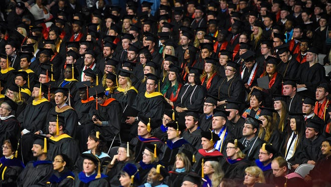 Graduates wait to receive their degrees during Friday's fall semester commencement ceremony at St. Cloud State University's Halenbeck Hall.