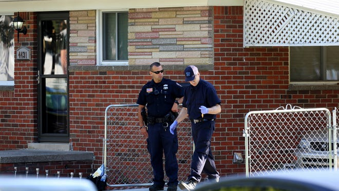 A Dearborn Heights police officer protects the scene of a quadruple murder at a house on Hipp Street near Annapolis as Michigan State Police medical examiners process and collect evidence Sept. 21, 2016.