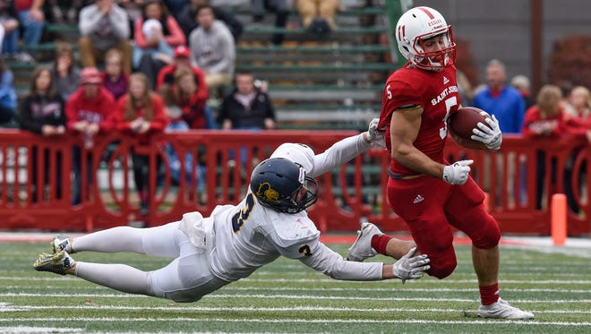 Adam Essler tries to escape a tackle by Mark Leedy of Carleton during the first half of Saturday's game at Clemens Stadium in Collegeville.