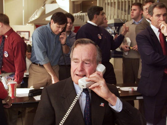 Former President George Bush makes a few phone calls Jan. 13, 2000, on behalf of then-candidate George W. Bush, during a surprise visit to Bush campaign headquarters in West Des Moines. The elder Bush spoke later Thursday at a dinner launching the Greater Des Moines Partnership.