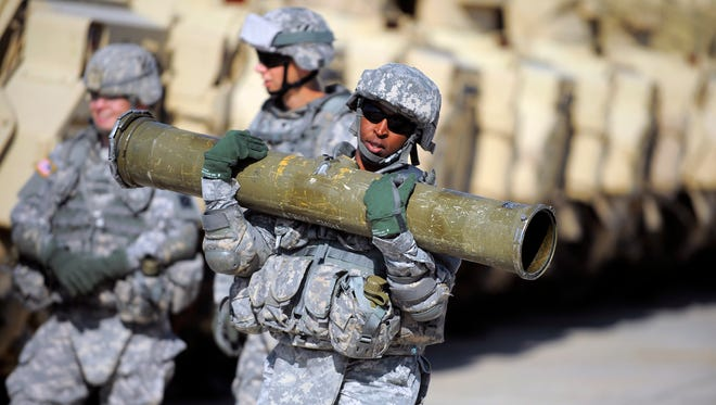 Army Cpl. Jacqueline Beachum carried a 65-pound dummy missile several yards before loading it on the launcher of a Bradley Fighting Vehicle during a physical demands study at Fort Stewart, Ga. The Army was conducting a study to determine how all soldiers, women and men, would be deemed fit to join its fighting units.