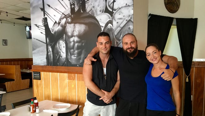 From left, owners Alex Koukouras, George Rozakis and Melis Rozakis pose in the dining room of Molon Labe Souvlaki in Fort Myers.