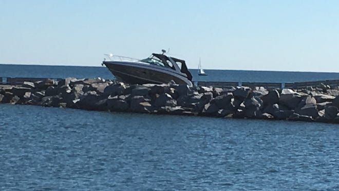 The boat that two men crashed into the break wall remained visible Saturday afternoon.