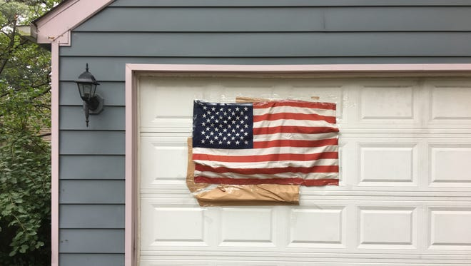 Brown paper and an American flag are taped over graffiti at a house Sept. 18, 2017 on West Farnum Avenue near Woodcrest Drive in Royal Oak.