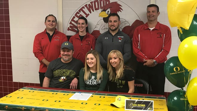 Westwood senior Sara Buchner prepares to sign her letter of intent on Wednesday, Nov. 8, 2017 to compete for the University of Oregon acrobatics and tumbling team. Seated next to Buchner are her parents, David and Michele. Back row, from left: Westwood AD Dan Vivino, gymnastics coach Jennifer Bulger, guidance counselor Vincent Aiello and principal Frank Connelly.