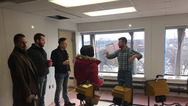 Rise & Grind partner Eric Jandrain, right, takes visitors on a tour of a private office available for rent in the co-working space.
