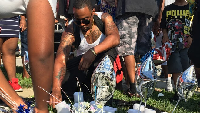 Joseph Campbell arranges items in a makeshift memorial for his cousin, Ronnie Campbell, who was shot and killed at a BP station near 34th Street and Moller Road on June 18, 2018. More than a week later, Campbell's family and friends joined the Ten Point Coalition to call for an end to gun violence.