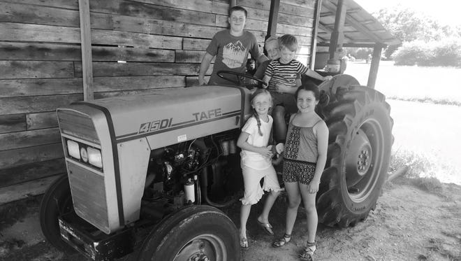 My cousins' children -- Pace and Callan Hutchinson, Jackson Palmer, Ivy Hutchinson and Isabella Casolera -- pose with an old tractor in their great-granddady's barn.