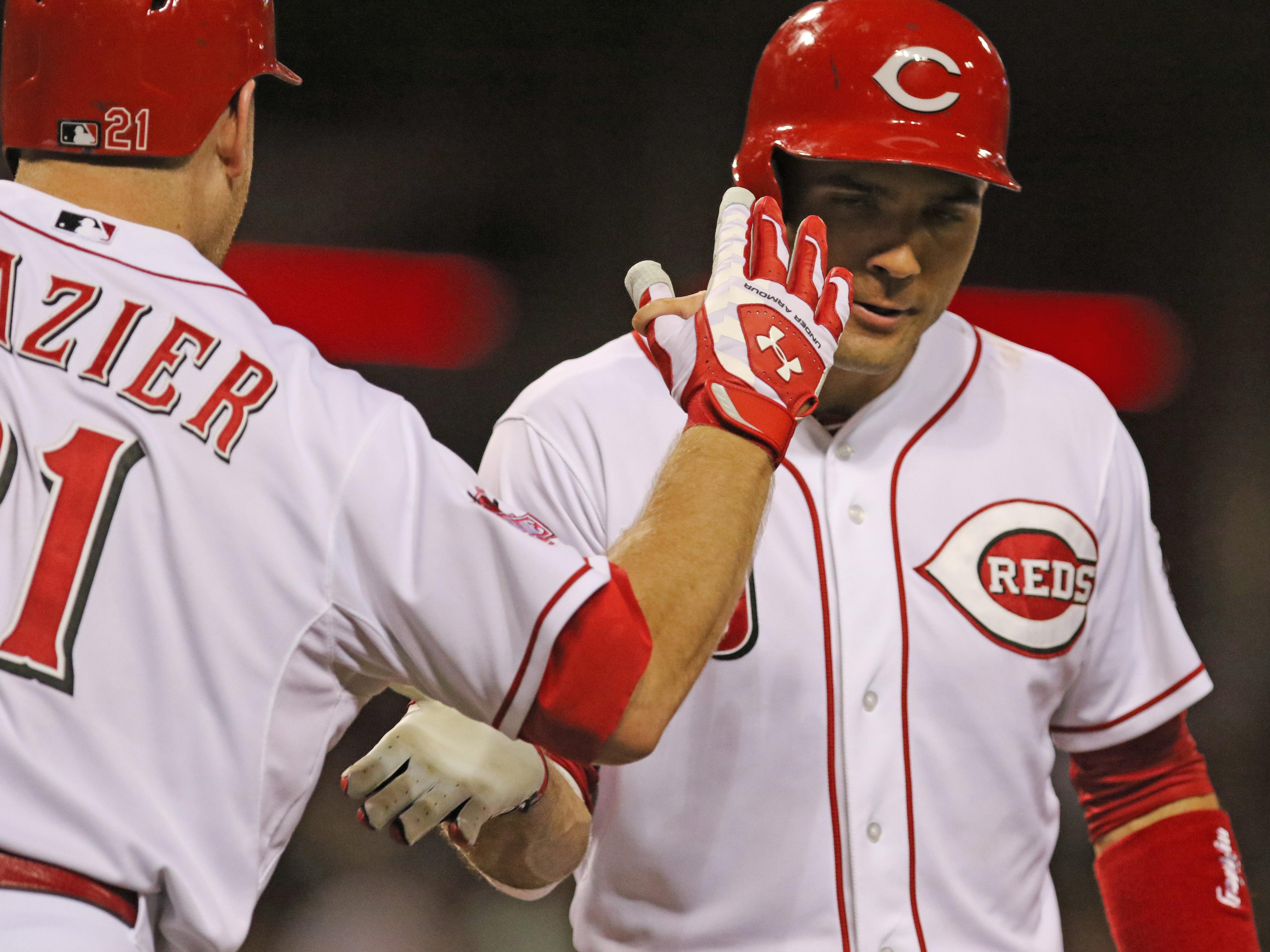 Cincinnati Reds first baseman Joey Votto (19) is congratulated by Todd Frazier after hitting a solo home run off Cleveland Indians starting pitcher Trevor Bauer (47) during Friday's game at Great American Ball Park.
