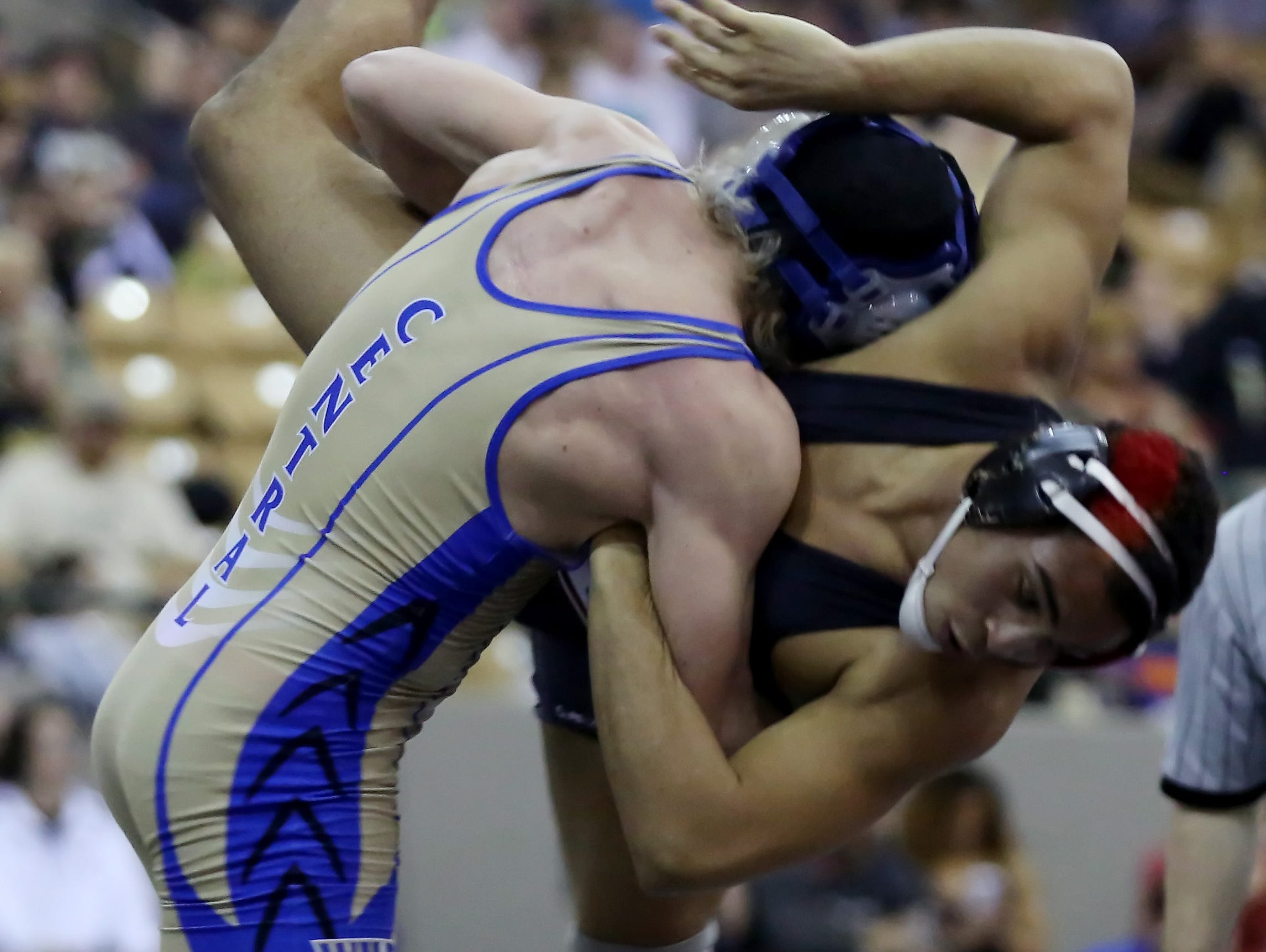 Wilson Central's Zach Linton, left, in blue and gold wrestles John Olivieri of Stewarts Creek, right, in black and red during the 170-pound semifinals at the TSSAA State Wrestling Tournament Friday.