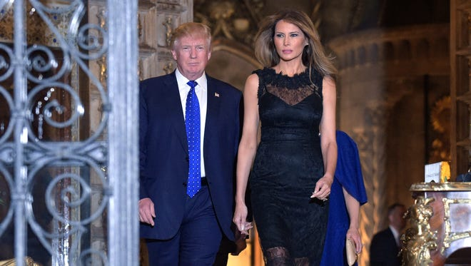 President Trump and first lady Melania Trump walk ahead of Japanese Prime Minister Shinzo Abe and his wife, Akie Abe, to pose for a group photo before dinner at Mar-a-Lago on Feb. 11, 2017.