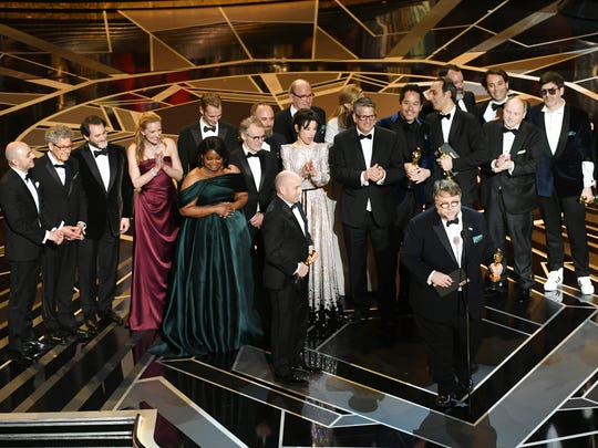 """Producer J. Miles Dale (left), director Guillermo del Toro (at microphone) and the cast and crew accept best picture for """"The Shape of Water"""" during the 90th Annual Academy Awards on March 4, 2018, in Hollywood, California."""