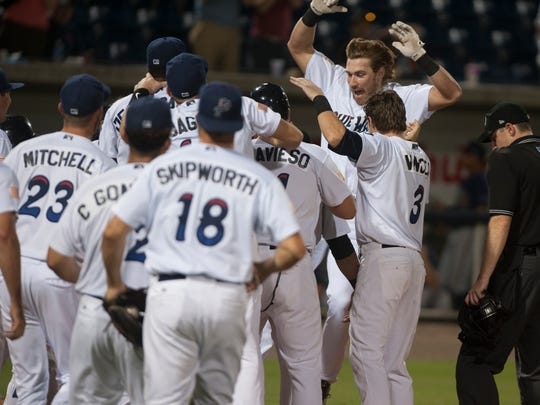 Teammates gather around home plate as Taylor Sparks comes in to score after hitting a walk-off home run in the bottom of the 11th inning during the Mississippi Braves vs. Blue Wahoos baseball game at Blue Wahoos Stadium in Pensacola, FL on Monday, July 11, 2016.
