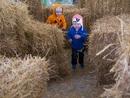 Madalyn Kirkwood, 4, chases after her nearly 2 year old brother, Cal, around a hay maze that was built for Boo at the Zoo at the Mesker Zoo.