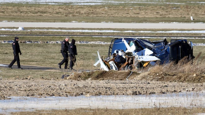 Brookfield police investigators survey the scene of a small plane crash at the Capitol Airport on Gumina Road Wednesday, Jan. 4, 2017. The pilot was killed and two others were injured when the plane crashed on takeoff, slamming into an SUV that was parked off of the runway.
