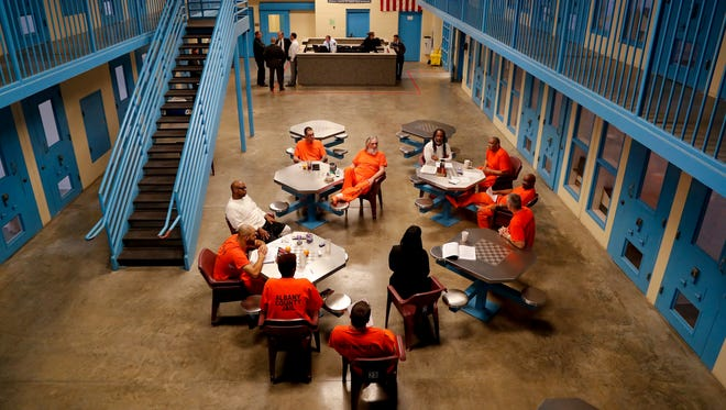 Inmates inside Albany County jail's veteran's pod gather for a group session with Sarah Polidore, center, executive director of field services for Moral Reconation Therapy, Monday, Nov. 27, 2017, in Albany, N.Y. Albany County's jail devotes one of its housing units for veterans, an increasingly common feature of state and county lockups as the criminal justice system focuses more on helping them reintegrate into society. (AP Photo/Julie Jacobson)