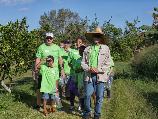 Kevin O'Dare, right, of Osceola Organic Farm, gives students from Youth Guidance and Hope for Families Center a tour of an orange grove.
