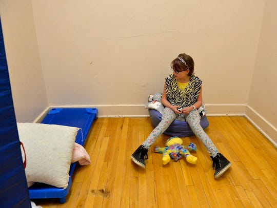 "Caitlin White, a sixth grader diagnosed with several mental and behavioral disabilities,sits in the ""calm down room"" which is available to students that need a quiet space to be alone, during an episode of extreme anxiety."