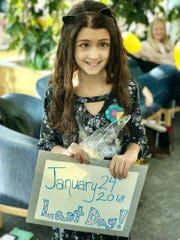 Brie Mestrovich holds a sign marking her last day of proton radiation therapy.