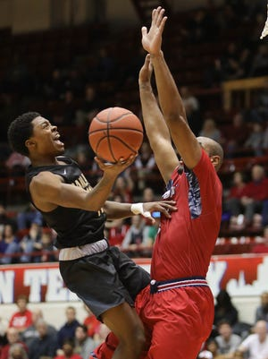 Oakland guard Brailen Neely passes against Detroit Mercy forward Roschon Prince during the second half Saturday, Jan. 20, 2018 at Calihan Hall in Detroit.