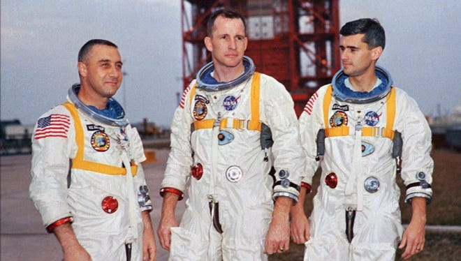 """Apollo 1 astronauts, from left, Purdue graduate Virgil """"Gus"""" Grissom, University of Michigan graduate Edward White II, and Purdue graduate Roger Chaffee pose next to their Saturn 1 launch vehicle in this Jan. 17, 1967, photo at Launch Complex 34 at Cape Canaveral Air Station in Cape Canaveral, Fla."""