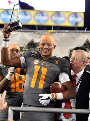 Tennessee quarterback Joshua Dobbs  holds the MVP trophy after the Vols' 38-24 win over Nebraska in the Franklin American Mortgage Music City Bowl at Nissan Stadium on Friday in Nashville.