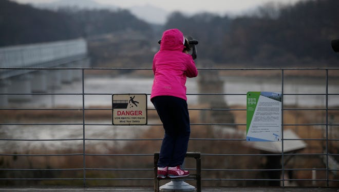 In this Feb. 14, 2016, file photo, a girl uses binoculars to watch the North side at the Imjingak Pavilion near the border village of Panmunjom, which has separated the two Koreas since the Korean War, in Paju, South Korea.