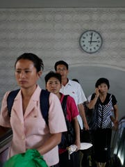 A clock hangs on the wall as North Koreans leave an underground train station.