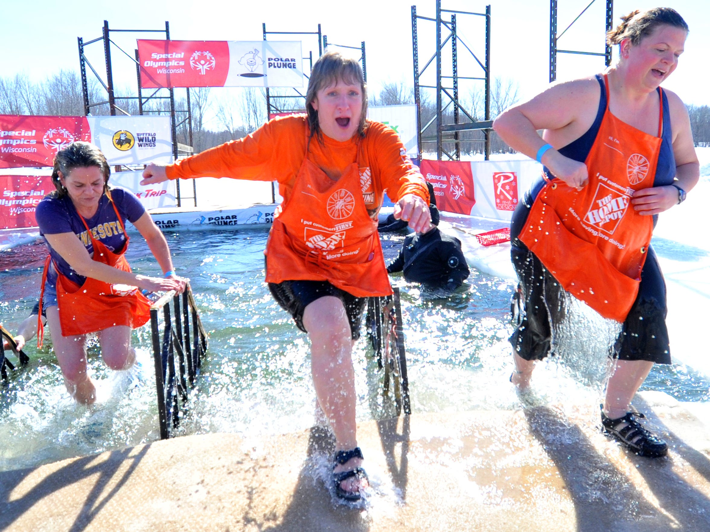 Amy Stanchik, from right, Sandy Haas and Ann Hamburg, all of Wausau, climb out of the frigid water during Saturday's Polar Plunge at Sunnyvale Park in Wausau. The annual event benefits Special Olympics Wisconsin.