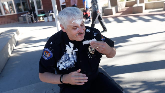 Farmington Police Chief Steve Hebbe wipes away whipped cream after taking a pie to the face Tuesday during the Farmington Police Department's National Night Out event at the Boys & Girls Clubs of Farmington headquarters.