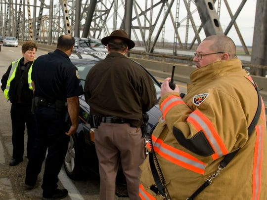 DENNY SIMMONS / THE GLEANER Bryan Coghill, asst. chief of the Henderson City/County Rescue Squad, (right) coordinates rescue boats from the southbound lane of the Twin Bridges over the Ohio River in December of 2015. A man was reported to have pulled his car over and leaped from the bridge into the swollen river. Rescue workers from Henderson, Evansville and Perry Township aided in the search and recovery, but they were unable to find the man.