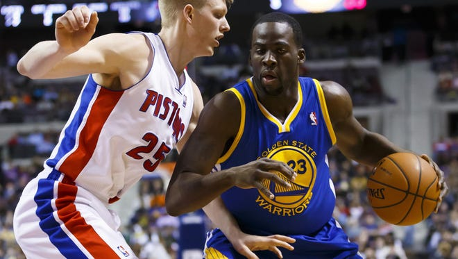 Golden State Warriors forward Draymond Green, right, dribbles the ball around Detroit Pistons small forward Kyle Singler at the Palace of Auburn Hills.