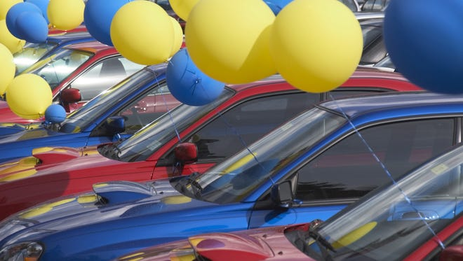 Balloons at a car dealership lot.