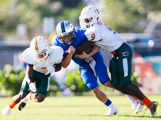 Dunbar High School defenders tackle Ida Baker's Luke Endsley recently at Ida Baker High School in Cape Coral.
