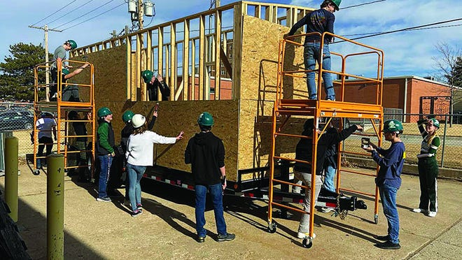 Pratt High School students in the geometry in construction class work on building a mobile Frog Shop for the sale of Greenback booster items. Several class members and teachers Tim and Melissa Rector presented a progress report to USD 382 board of education members at their February meeting.