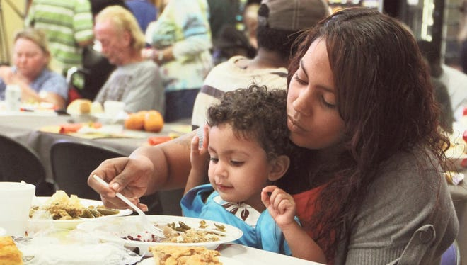 Doris Acevedo, and Aracelis Acevedo, 1, partake in a Thanksgiving meal at the Salvation Army in Fort Myers on Thursday.