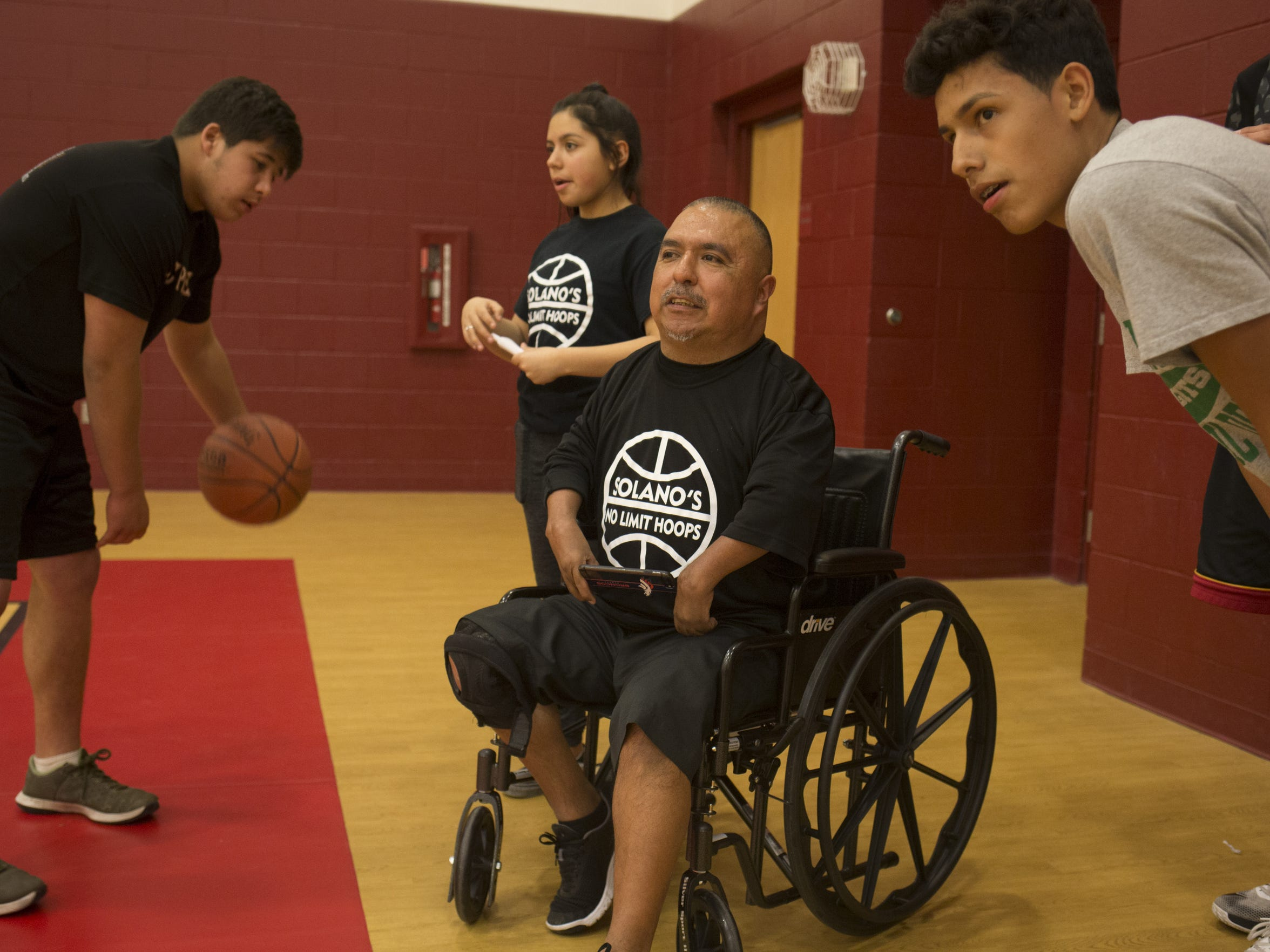 David Solano, center, talks with Eddie Martinez, Jr. during Solano's No Limit Hoops in February.