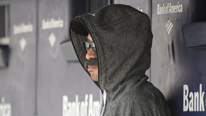 Ichiro Suzuki wears a fake mustache and a hoodie as he sits in the dugout and watches Thursday's game.