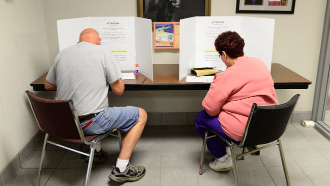 Marvin, left, and Sandi Arndt of Clyde vote at the Board of Elections in Fremont on Wednesday, the first day for early voting in the Nov. 7 General Election. For information on voting call the board of elections at 419-334-6180  or go online to sandusky-county.com.