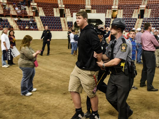 A protester is escorted out of the Farm Show complex