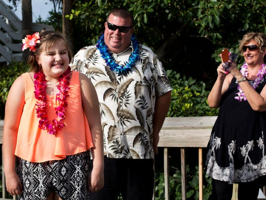 Victoria Law, 9, who has leukemia, smiles alongside her parents, Richard and Patricia, as she arrives at a surprise luau send-off party sponsored by The Ritz-Carlton, Naples before her Make-A-Wish trip to Hawaii on July 31, 2015.