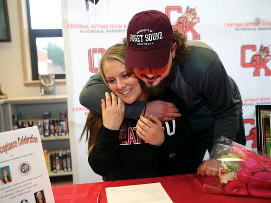 Central Kitsap soccer player Lauren Hudson gets a hug from CK football player Reece Wood after they both signed college sports letters of intent on Wednesday. Hudson will play for Seattle University and Wood for the University of Puget Sound.