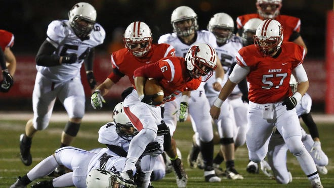 Kimberly's Blair Mulholland (6) follows the blocking of center center Travis Merckx (57) during a WIAA Division 1, Level 3 football playoff game against Fond du Lac at Papermaker Stadium on Nov. 7, 2014.