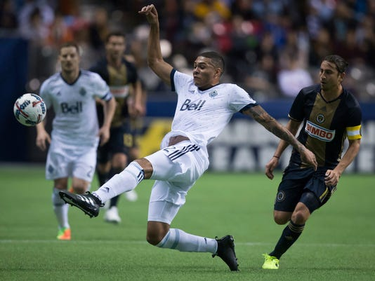 Vancouver Whitecaps' Christian Dean, center, kicks the ball away from Philadelphia Union's Alejandro Bedoya, right, during the first half of an MLS soccer game in Vancouver, British Columbia, Sunday, March 5, 2017. (Darryl Dyck/The Canadian Press via AP)