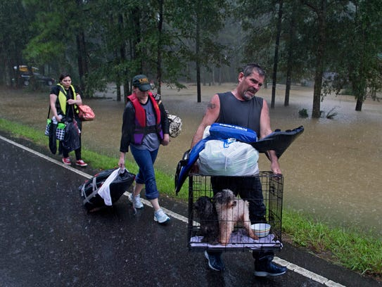 People arrive to be evacuated by members of the Louisiana